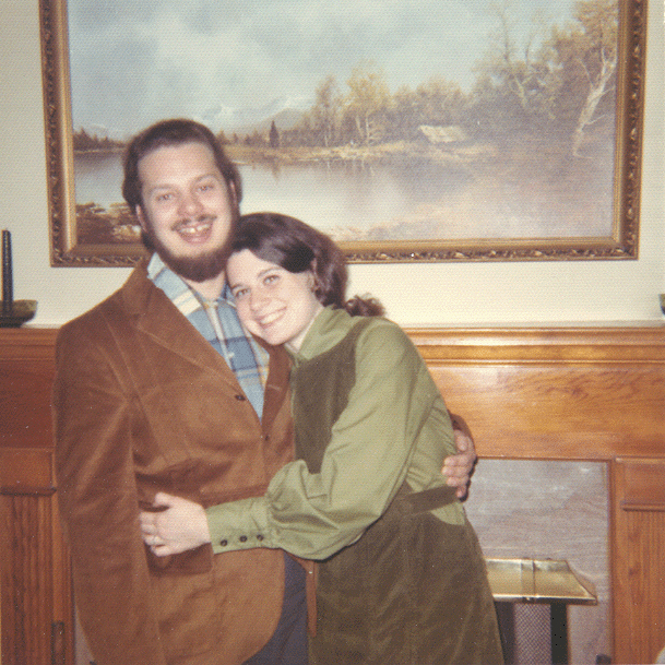 A young Carol dressed in a green jumper is hugging Charles who has a full beard and is wearing a corduroy jacket and a plaid shirt. They both have big smiles after becoming engaged in 1970.