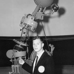 Charles Legg, wearing a suit and tie is standing at the base of the COSI Planetarium projector when he was 15 years old.