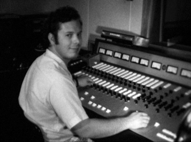 Charles is seated at a W O S U radio station control console in 1970. He is adjusting the knobs and slider controls on the control board as he is looking back over his shoulder.