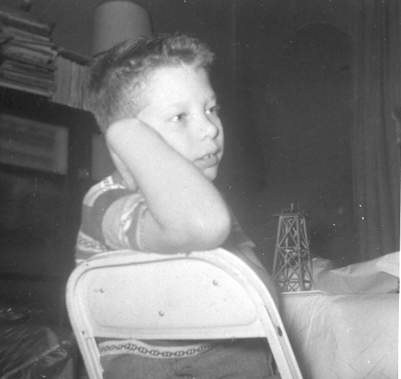 A 10 year old Charles is seated at a metal chair and is looking back over his arm while holding his head up with his hand. He has a day dreamer look about him.