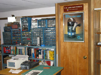 Shelves of book are seen with many small part drawers sitting on top that contain electronic parts. There is also a storage closet with a personal robot on the door.