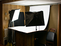 A small photography studio with soft box lights on either side of a white backdrop used for photographing items for sale on eBay.